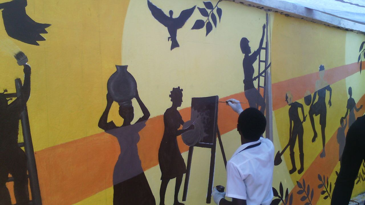 One of the local artists puts finishing touches on the Bukavu mural.