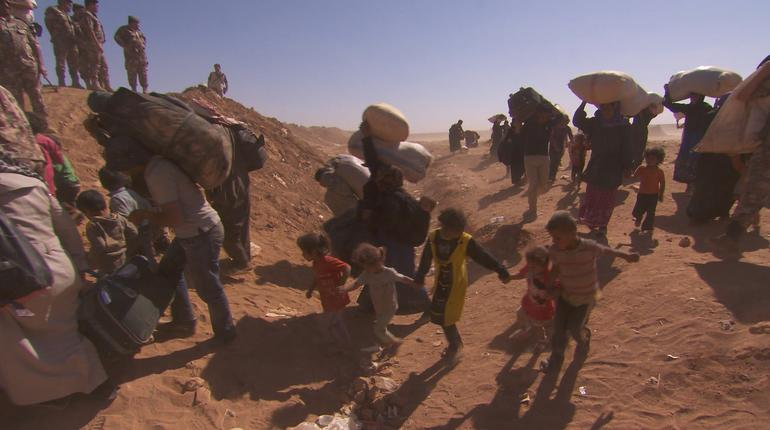 Syrian refugees crossing the Jordanian border in search of food and safety.