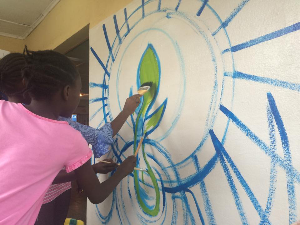 Some of the Matumaini girls help paint the mural.