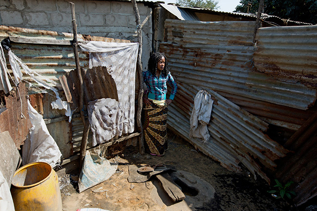 "Flora, a high school student in Mozambique, shares a bathroom with several families, including her own. She says that she ""hate[s] using this toilet. Sometimes men peek over the fence. There is no privacy.""  (Credit: James Oatway)"