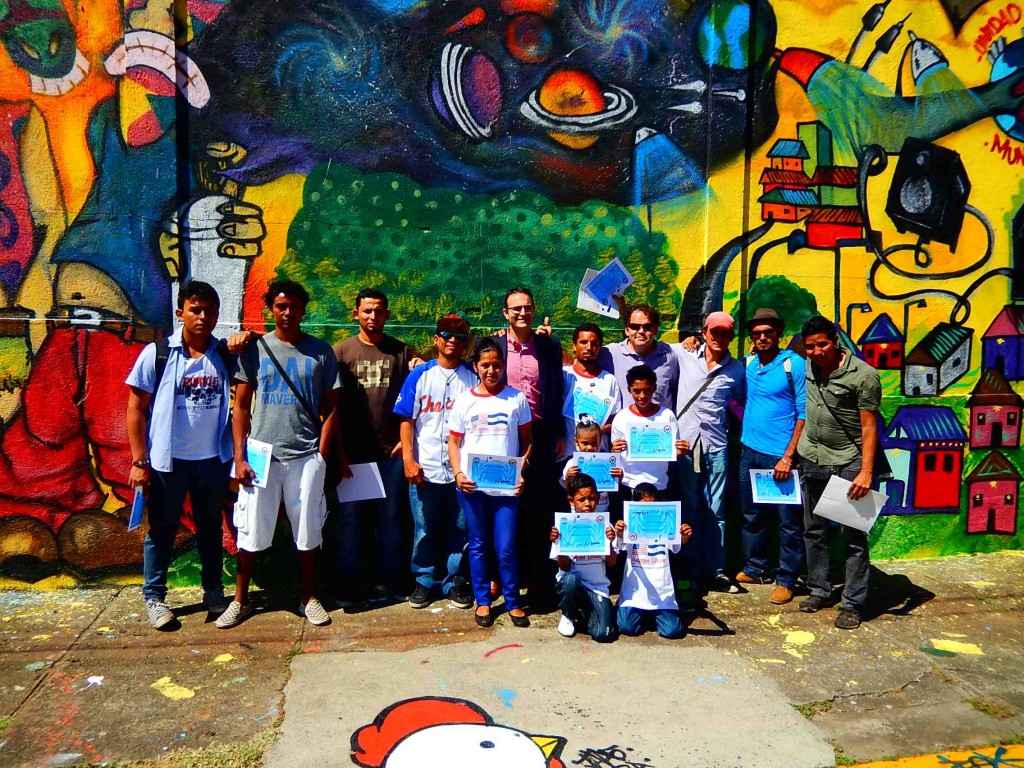 Program participants with their diplomas in front of the completed mural.
