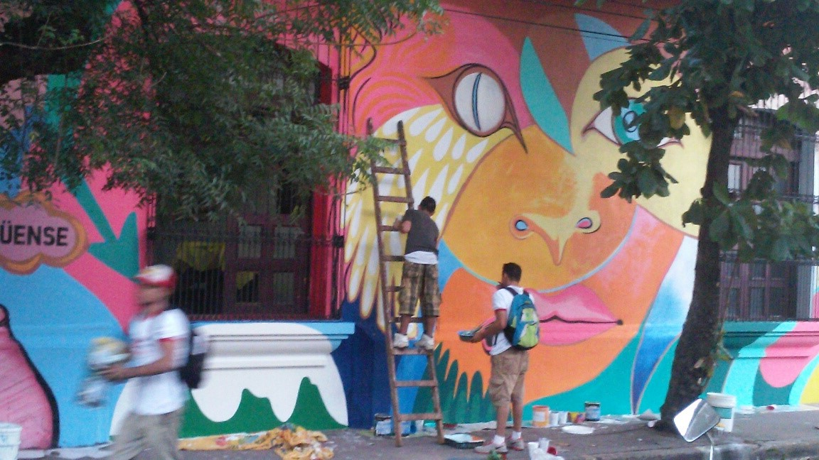 Local youth working on the main feature of the wall, the face of a half-lion, half-woman.