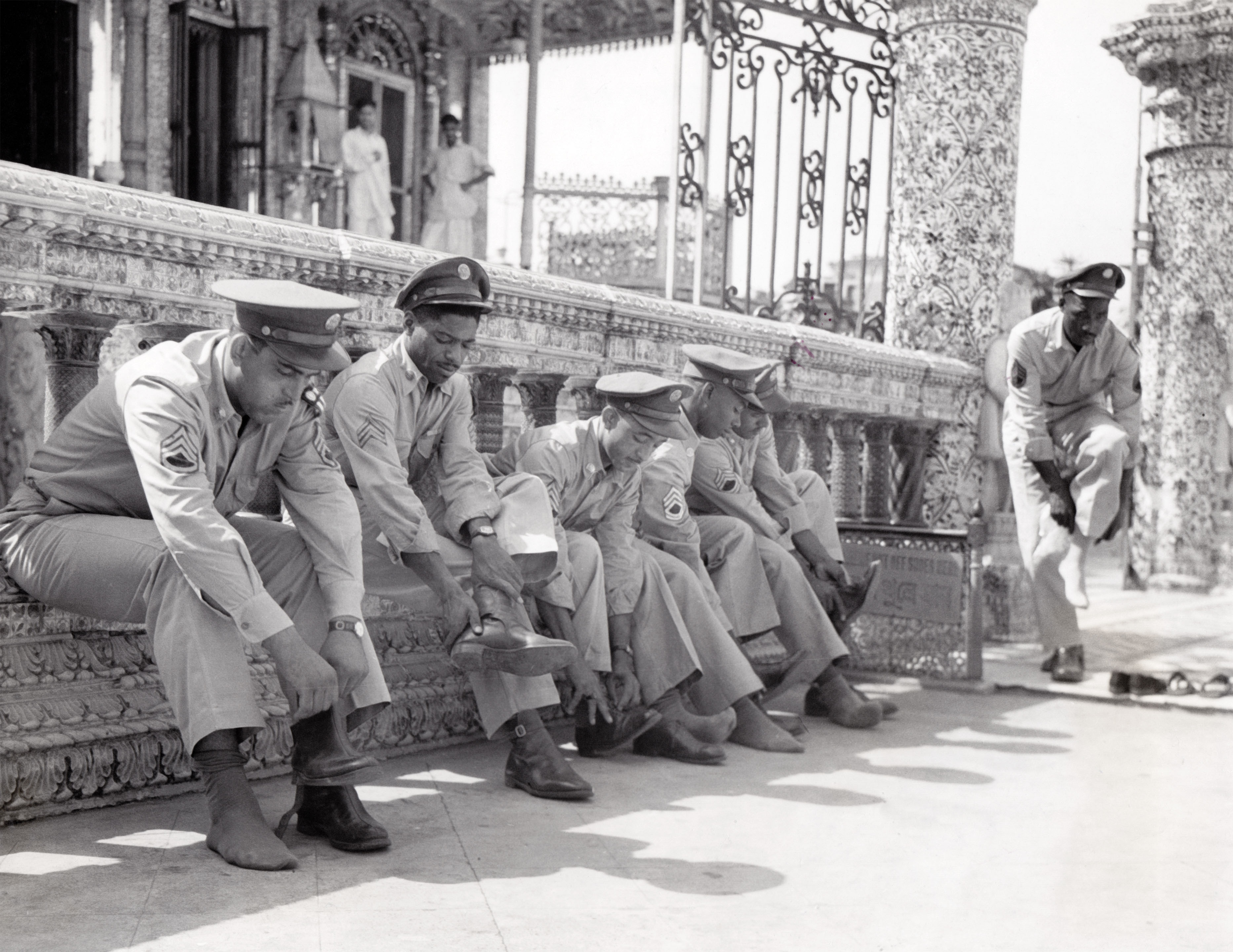 U.S. soldiers respectfully remove shoes before entering the Calcutta Jain Temple, 1943 Calcutta, West Bengal