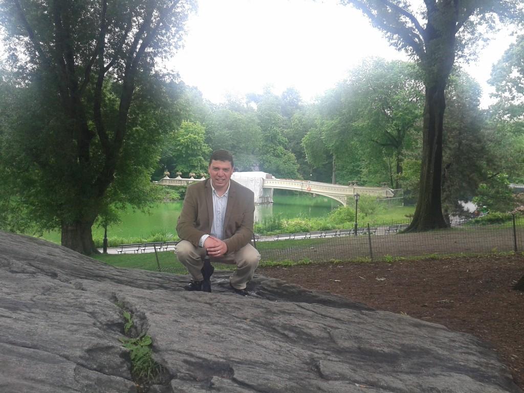 Pedro Prado kneeling in Central Park