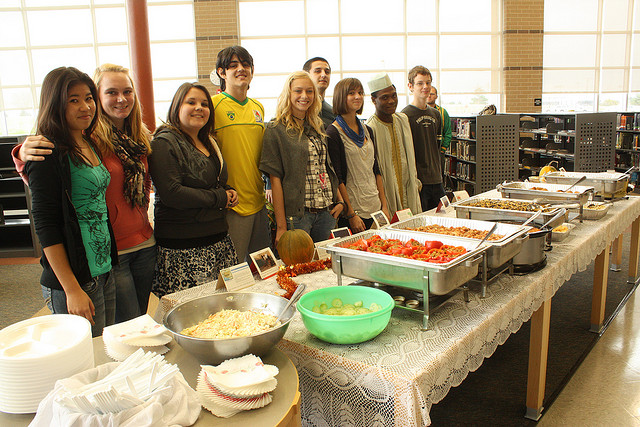 High School exchange students prepare a feast of food from their home countries for their classmates in Iowa (Photo Credit: Carol VanHook)