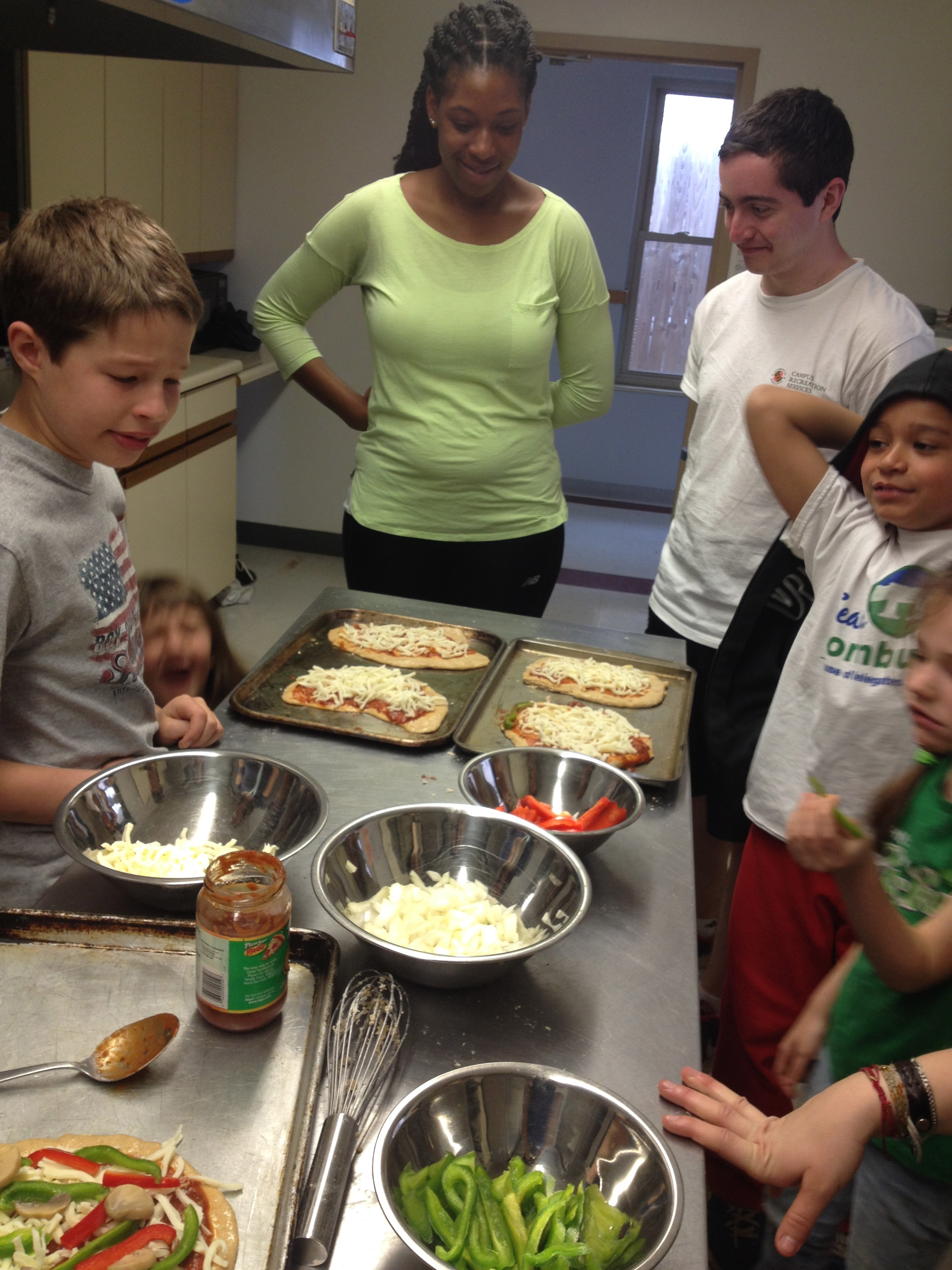 University of Maryland students make pizzas with young children at School Age Connections in Huntington, WV.