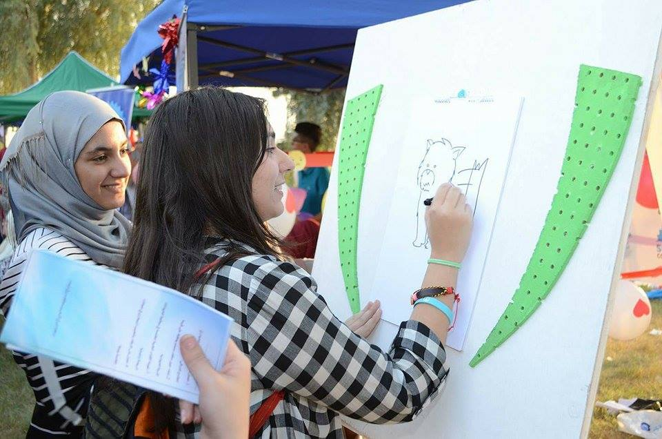 People drawing their favorite animals at Ibrahim's booth during the Baghdad City of Peace Festival.