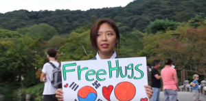 "Wearing traditional Korean clothing, and donning a sign that said, ""I'm Korean. Won't you give me a hug?"", Suyeon Youn demonstrates a level of soft power diplomacy."