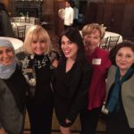 Fadia Thabet (left) and Saadet Özkan (center) pose for a photo at the American Women for International Understanding reception.